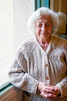 Portrait of old lady by the window, smiling and looking at the camera.