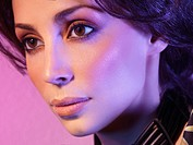 Closeup portrait of a beautiful woman face with artistic makeup and colored purple light.