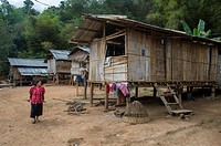 A local woman is walking in front of traditional houses on stilts made from bamboo in Ban Muangkeo Village, a cultural heritage village on the Mekong ...