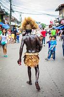 Filipino man with his body painted black with soot, walks down the street holding a religiuos icon of Santo Niño during Ati-Atihan festival, Kalibo, A...