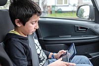 Boy,10 years old, plays computer game in car,UK.