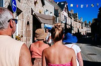 Tourists walking on street full of traditional fifteenth-century stone houses. Morlaix, Brittany, France.