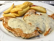 Pork steaks with cheese sauce and fried potatoes. Close view.