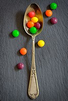 Colorful jelly candies in spoon on ardesia plate.