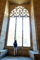 Tourist looking through one of the windows of the Long of the Silk, Valencia, Spain