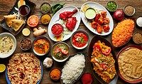 Assorted Indian recipes food various with spices and rice on wooden table.