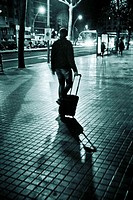 Rear view of a man carrying his suitcase on wheels behind him in a street at night. Barcelona, Catalonia, Spain.