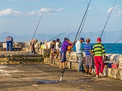 Men fishing off the harbor wall on a Sunday afternoon. Kalk Bay fishing Harbor, Cape Town, South Africa.