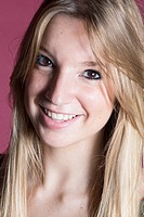 Studio portrait of happy young woman with long blond hair Studio portrait of happy young woman with long blond hair on pink background.