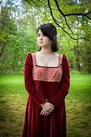 Young woman, standing in a park, wearing a long red vintage dress.