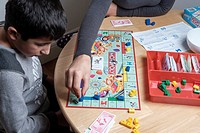 Mother and child playing monopoly board game.