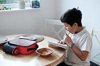 Schoolchild,9-10, reads a book and snaks on crisps,UK.