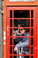 woman, 60, on her mobile phone in a British phone booth, Commercial Drive, Vancouver, BC, Canada.