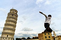 Tourist posing in front of Duomo and Leaning Tower of Pisa, Italy.