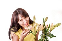 A pretty woman smells and enjoys the scent of yellow lilies.