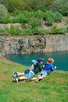 Three boys lie on the edge to a lake in an old stone pit in Bornholm, Denmark.