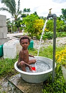 Child boy bathing in in a large metalic bowl in a garden, Efate island, Port Vila, Vanuatu.