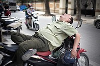 Man sleeping on his bike, Hanoi, Vietnam.