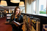 Rotterdam, Netherlands. Young, brunette and caucasian immigrant woman from the Ukraine, visiting the Public Library to read and learn the Dutch langua...