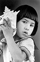 Young girl listening to conch shell