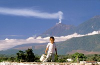 Mayan boy and the Volcán de Fuego in background. Antigua Guatemala. Guatemala