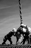 Ironworkers attaching load to crane. I-880 Cypress Project. Oakland, California. USA.