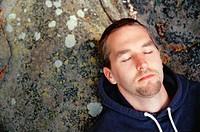 Man asleep on rocks. Mayne island. British Columbia. Canada.