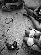 Brothers and sisters sit on the rug playing video games. Some anxiously await the turn at the remote. All watch the TV.