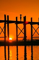 Silhouettes of people walking across the iconic U-Bein bridge over the Taungthaman Lake at sunset, Amarapura, Myanmar. The U-Bein Bridge at 1.2 km. (3...