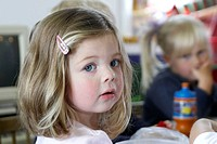 3 year old girl, looking into camera, at nursery, serious,