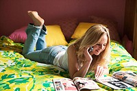 Barefoot blonde teen girl laying on bed reading magazines, talking on cellphone, and listening to i-pod.