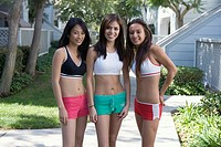 Three smiling teen girls in bare-midriff exercise outfits.