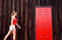 Woman walks toward red door