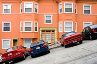 Cars parked in front of a bright, well_maintained orange house on a very steeply sloped section of Jones Street in San Francisco, California. The stre...
