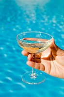 Hand holding champagne glass in front of pool.