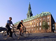 Cyclists in front of the castle of Christiansborg,  Copenhaguen, Denmark