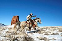 Cowboy out for a ride in winter, Shell, Wyoming. Usa