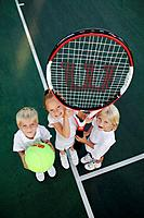 Kids posing with an oversized tennis racket and ball