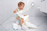 Llittle girl sitting on Potty in bathroom, unrolling toilette paper while doing potty training, playing and fooling around
