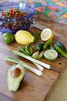 Scallions, lemons, limes, chilis, avocado, on chopping block. Bowl of diced veggies in background.