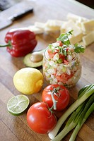 Glass of ceviche, tomatoes, lemon, scallions & lime in foreground, sliced cheese, bell pepper, & avocado in background.