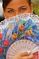 A portrait of a young girl posing with a colorful fan.
