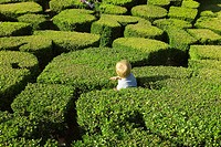 France, Ile de France, park of Breteuil castle: child playing in the hedge