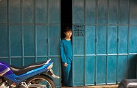 Young Indonesian girl in the doorway of her home in the city of Tanjungpinang on Bintan island, Indonesia