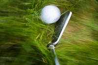 GOLF Blurred motion of club and golf ball in heavy grass on course in Deerfield, Illinois