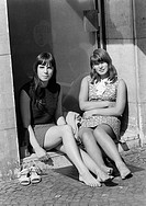 Sixties, black and white photo, people, two young girls, aged 16 to 18 years, woman friends, girlfriends, sitting in a porchway and enjoy the sun, bar...