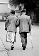 Eighties, black and white photo, people, elder people, older couple walking arm in arm, jacket, trousers, skirt, hat, aged 65 to 75 years