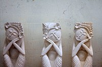 Three white stone figures of women that seem to be sleeping in sitting positions in Ubud, Bali.