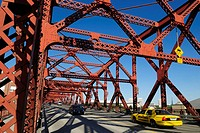 yellow cab and cars crossing a historic steel bridge over Willamette River, Portland, Oregon, USA