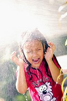 A little girl splashed wit h water from a hose pipe